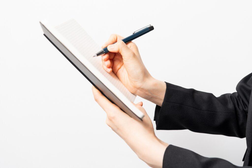 ノートにメモを取る女性の画像