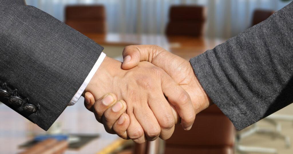 男性2人が握手している画像